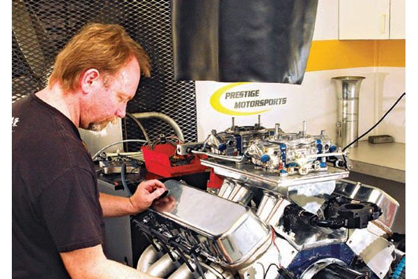 Fig. 7.1. Head porter Gil Mink readies this Prestige Motorsports 496-ci street engine for dyno testing. After an expert calibration this 2 x 4 carburetion system, using two QFT 650 carbs, produced results close to that expected of fuel injection. The top-end numbers produced demonstrated about 30 hp more than a typical single-plane single-carb intake.
