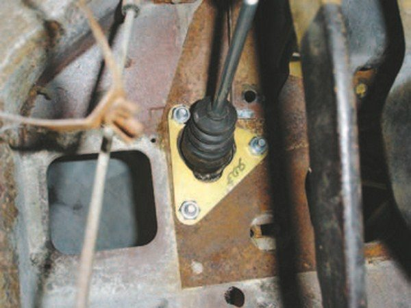 The back side of this clutch master cylinder uses an additional reinforcement plate to stiffen the firewall. The reinforcement has the same configuration as the master cylinder, so the bolts go through the firewall, cylinder, and plate. You need someone to hold the cylinder and the bolts in place while the plate is installed with the nuts. The clutch cylinder pushrod slides over the original clutch pedal linkage pin and uses a supplied retainer to hold it in place. Some kits require you to remove the clutch pedal assembly and push out the existing linkage pin. That sounds easy enough until you try to remove the pedal. Due to design, the dash cluster must come out first, then the clutch/brake pedal support is removed, starting under the hood. Four 1/2-inch hex-head bolts retain the support and can be found in the driver-side wiper pivot area (usually covered with undercoating concealing them). The master cylinder (or brake booster if power-brake equipped) is removed. Manual brake cars have two more 9/16-inch hexhead bolts to remove from the firewall above the master cylinder. Finally, two more 1/2-inch hex-head bolts are removed from the support under the dash, and it can be wrestled out. The linkage pin requires grinding and then hammering out. If a press is available, it is much easier to push out. While the pedal support is out, I usually replace the pivot bushings.