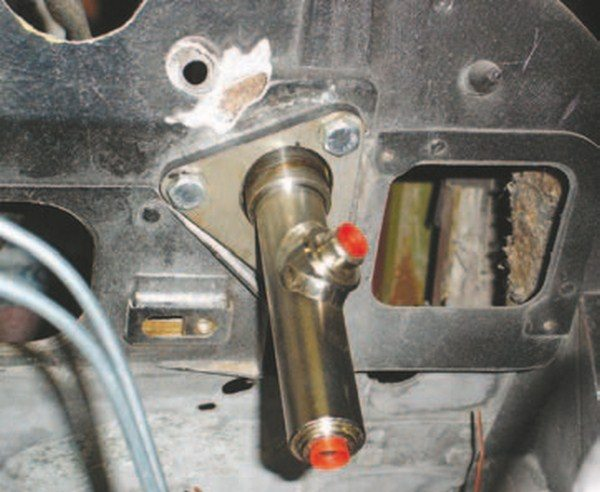 An aftermarket Wilwood hydraulic clutch master cylinder is fitted to a 1972 Shark before the body is installed. Converting from automatic transmission to manual transmission was the reason for this installation. American Powertrain has a complete ready-to-go kit that bolts in the same fashion as this assembly. The trick was getting the correct push point on the clutch pedal for the clutch pedal feel but American Powertrain has that figured out. The mounting plate fits in the original clutch boot's area without any modification. The original clutch linkage through the firewall boot is removed, then the hydraulic clutch master cylinder is installed using the original screw holes as guides. The port at the end of the cylinder receives the clutch flex hose to the hydraulic slave cylinder. The port in the center is for the fluid from the reservoir; it uses a flexible rubber hose that is impervious to brake fluid.