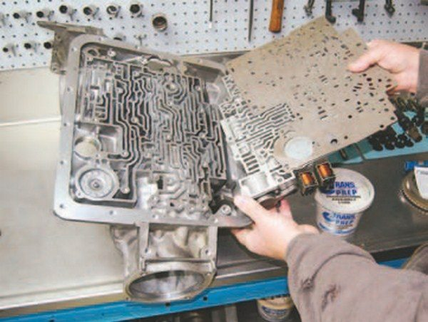 Once the pan and filter have been removed, valve body removal is next to access the separator plate. The separator plate has two gaskets, one for the case and one for the valve body. They must be removed for proper sealing. Carefully clean the gaskets. Watch for steel check balls as the valve body and plate are removed; they must be put back in the same location. Some shift kit separator plates omit some of the check balls. Be sure to read the instructions carefully before beginning the install. Go easy on the valve body bolts; 110 in-lbs (or 20 ft-lbs) is the maximum torque.