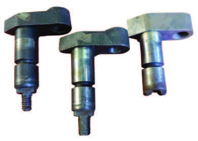 Muncie shifter shafts have evolved in three basic stages. From the left, the small 5/16-18 threaded stud, which snapped easily. The newer 3/8-24 stud still had to fit the rectangular keyway of the linkage arm, and so it had flats milled on each side, but they still broke. The last revision was a bolt-on shaft using a standard 3/8-16 threaded hex head bolt.