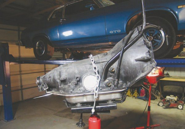 Our transmission is in place, strapped down, and ready to safely install in the vehicle.