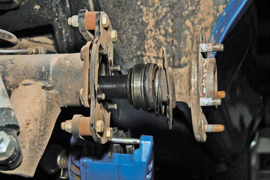 Bolt-in axles include (right to left) the axle, retainer plate, split washer shim, press-on bearing, and housing end. To remove the axle shafts, you need to remove the four bolts.