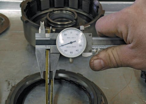 Use a dial caliper to measure the total thickness of one friction and one steel plate. You can then use this measurement when machining apply pistons to add more frictions to a clutch drum, or just to compare the dimensions of your replacement parts.