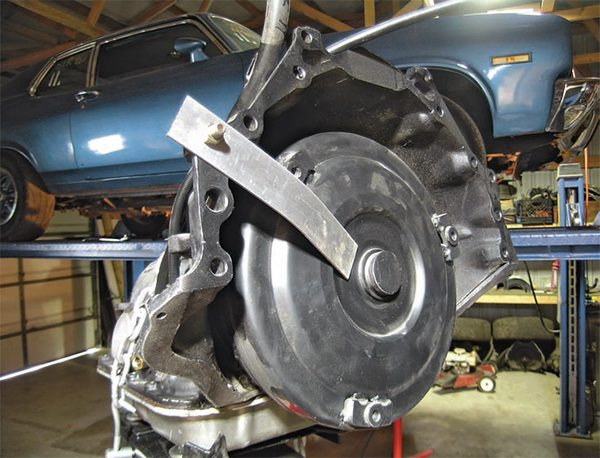 Use a retaining strap to keep the torque converter from falling out of the transmission until you are ready for the installation. A piece of aluminum flat bar with a 3/8-inch hole in it works well for this purpose.