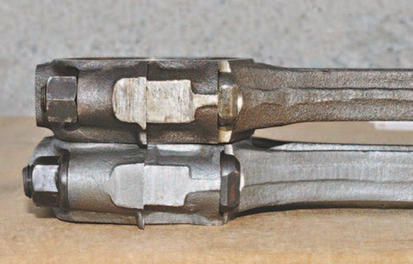 This side view shows the larger 7/16-inch bolt rod and upgraded nut with built-in washer face (bottom) compared to the 3/8-inch bolt rod (top). An important difference is the increased amount of material wrapped around the bolt on the large-bolt version.