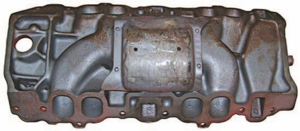 This bottom view of a 1970–1972 cast-iron intake shows the ovalport layout and the sheet-metal splash shield installed with rivets. The shield was designed to keep hot oil from heating the plenum, but the runners are unprotected and the exhaust-heat passages tend to cook oil that finds its way above the shield. A nasty charred mess accumulates right above the lifter gallery. (Photo Courtesy Vintage Big Blocks)
