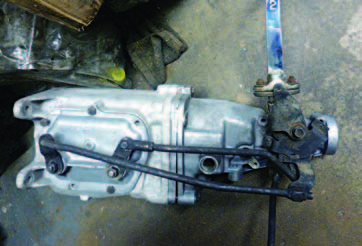 "This is essentially an original 1964 442 Oldsmobile Muncie casing with the original factory shifter. The sidecover pivot pin has no ""hat"" and can fall into the transmission. The speedometer fitting is located right where the linkage is. It's also below the oil level and prone to leaks. By 1966 it was relocated to the upper passenger side."