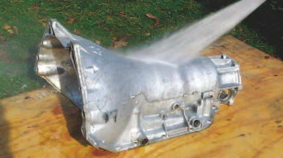 """A power washer makes a great transmission case cleaner. Using a """"zero"""" tip, a good power washer blasts off dirt and grease and makes the cleanup process a lot easier."""