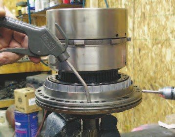 You need high-pressure air to blow parts dry after cleaning. It can also be used to pressure test the clutch pack operation. By applying air to the fluid supply holes, you can pressurize the passages with air and verify apply piston movement and whether the seals leak.