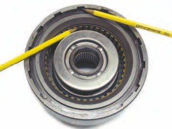 Within the TH400 direct clutch pack is an apply piston with seals, spring cage, snap ring, steels, frictions, backing plate, and retaining ring. Pressurized oil is routed behind the apply piston, forcing it to move toward the steel and friction plates. Note that the steel plates are notched on the outer edges, while the frictions have internal teeth. When the clutch pack is fully compressed, it effectively locks the drum to the component that has splines engaged with the frictions. In this case the component is the forward clutch, so both components turn at the same speed.