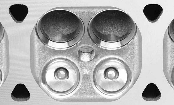 A 4-valve head offers greater flow curtain area since more of the chamber is filled with valves. This increased flow curtain area, combined with smaller intake ports with higher velocity curves, is why 4-valve heads always offer increased power potential. This is a shot of the combustion chamber on a GM 4.6L Northstar 4-valve engine.