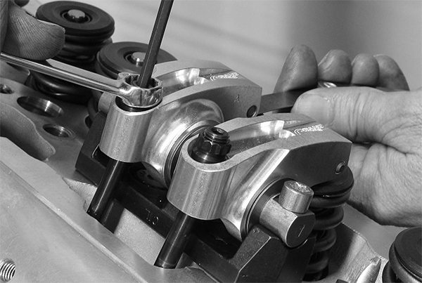 Setting lash with a rocker shaft system is accomplished with a simple feeler gauge and setting the clearance with the adjuster located on the pushrod side of the rocker.