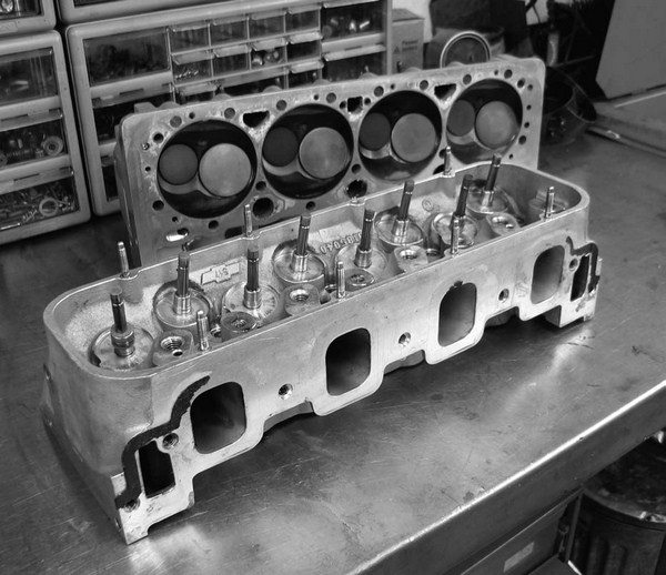The splayed valve head uses a symmetrical port layout that equally spaces the intake ports by using the intake-exhaust-intake-exhaust valve layout as opposed to the OEM layout that adjoins the two center exhaust ports in the middle of the cylinder head.